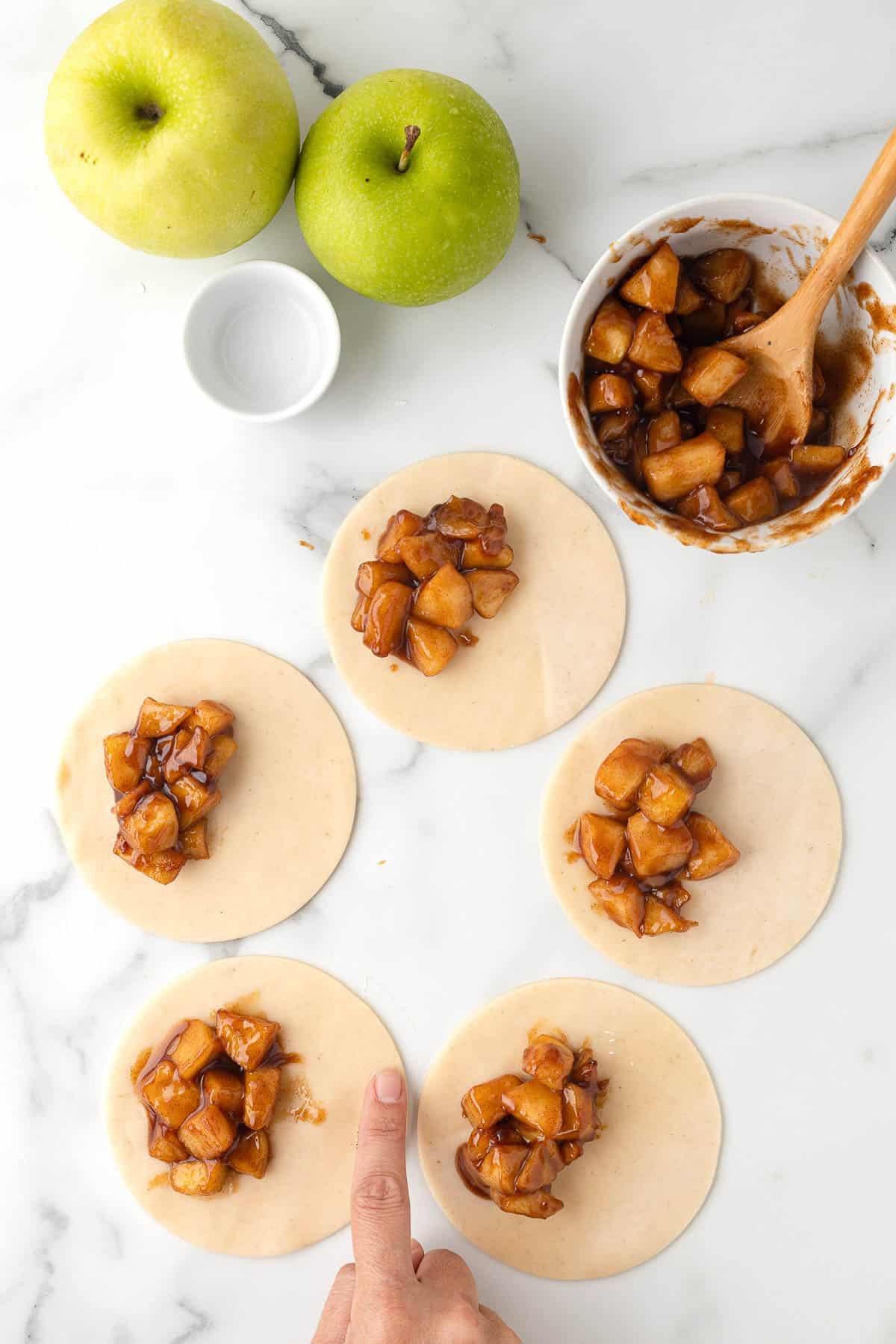 dough rolled out into circles and topped with apple pie filling to make individual apple pies
