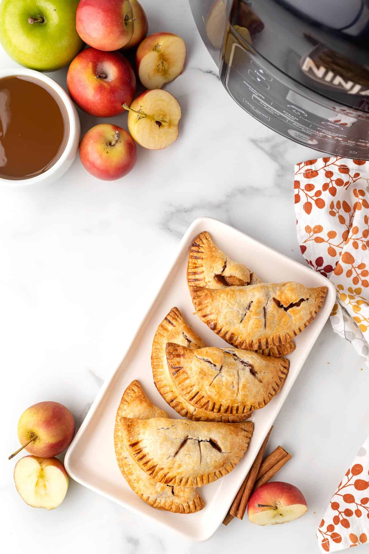 a white platter full of mini apple pies made in the air fryer  with apples in the background