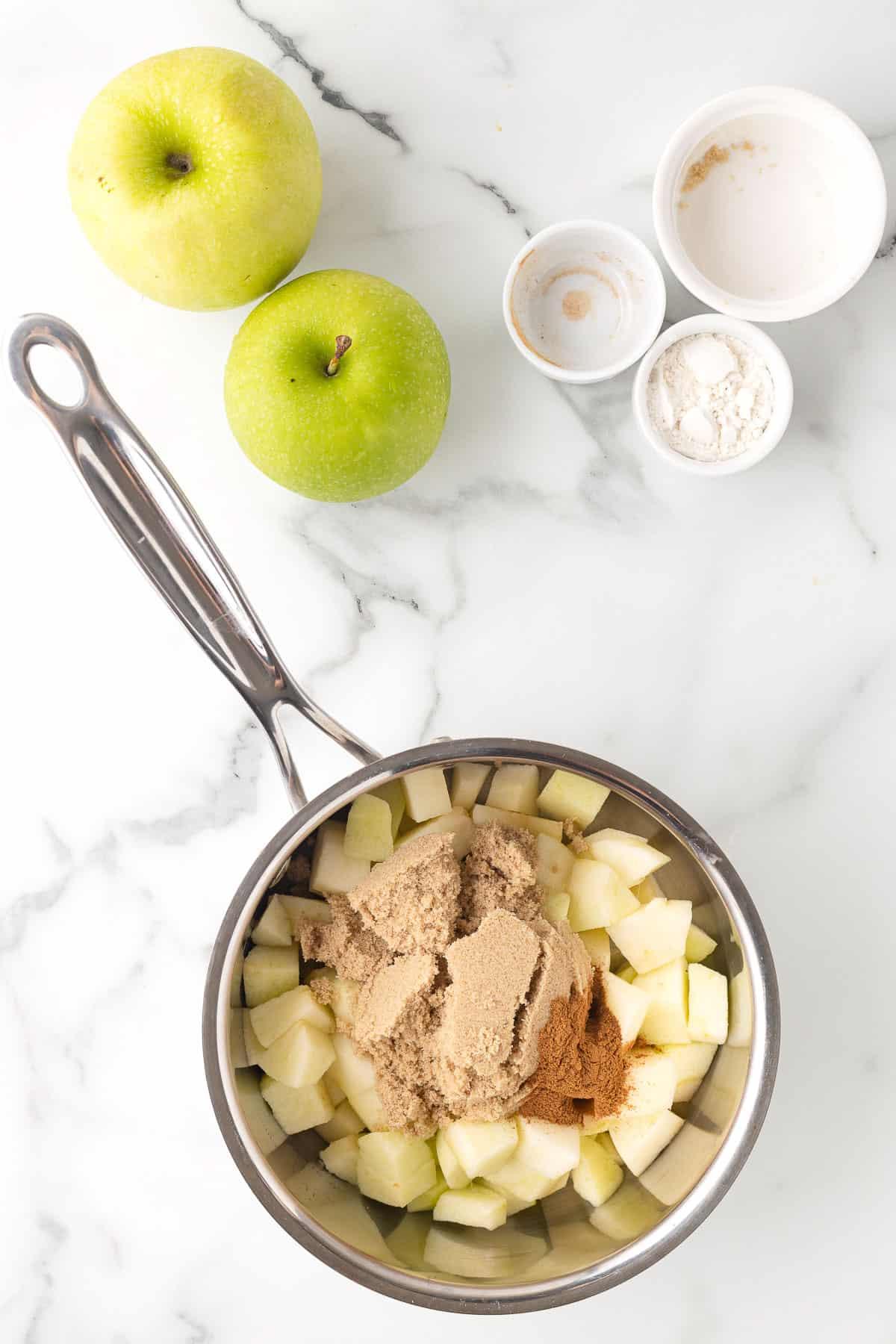 sauce pan with apples, brown sugar, and cinnamon to make apple pie