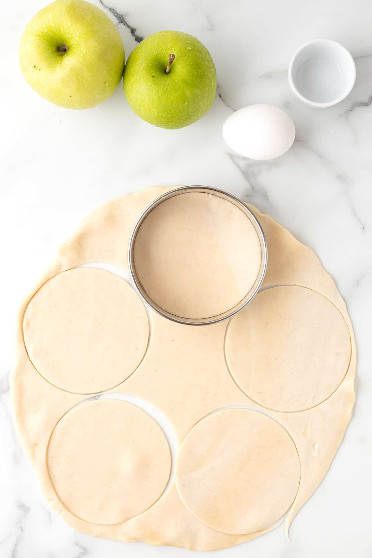 dough rolled out into circles to make individual apple pies