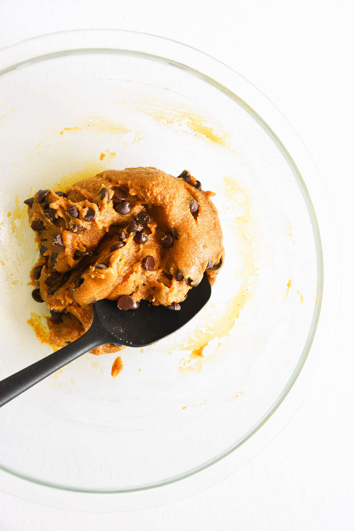 a mixing bowl full of gluten free chocolate chip cookie dough, loaded with chocolate chips