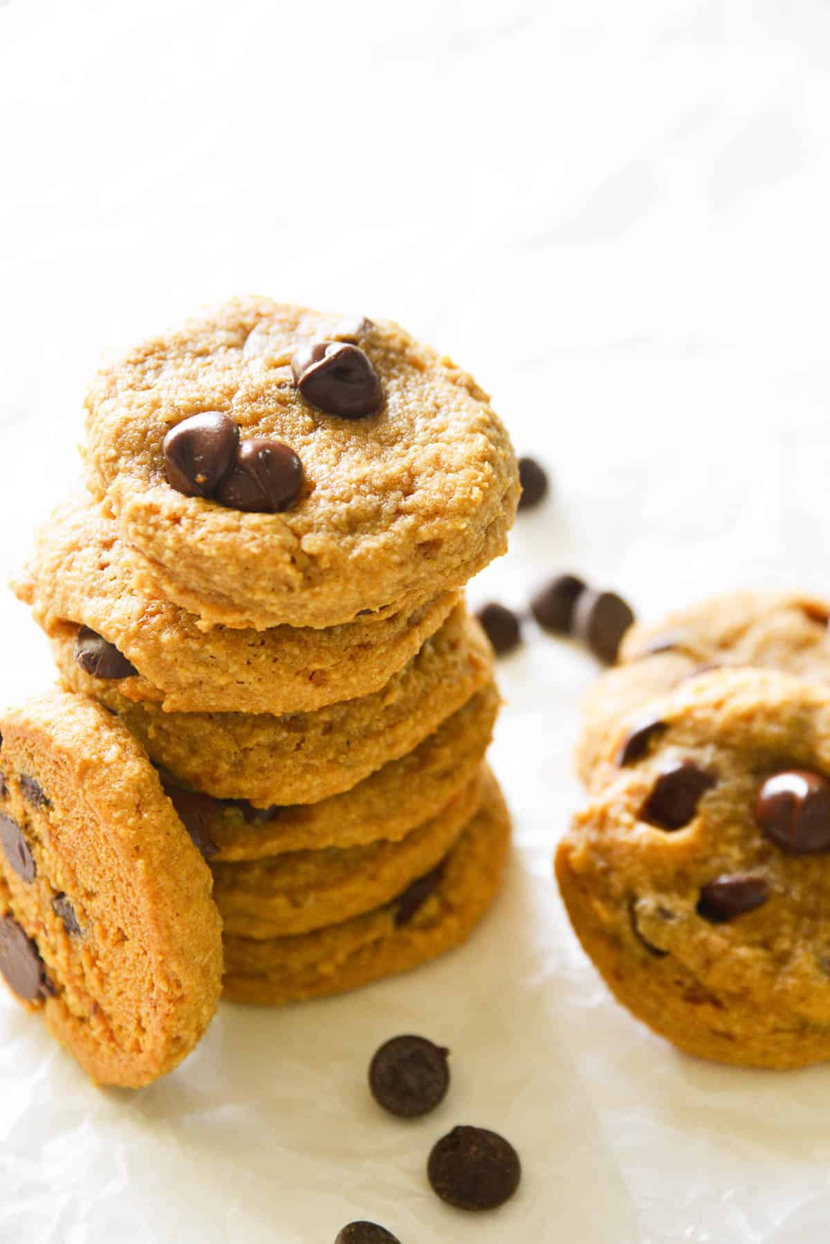 a stock of chocolate chip cookies, surrounded by chocolate chips