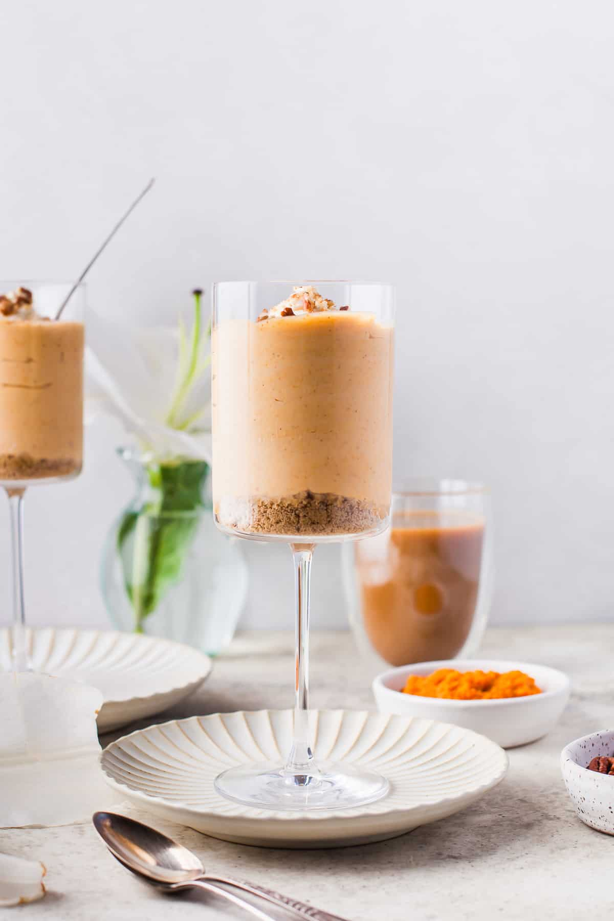 a large wine glass, filled with a pumpkin mousse, topped with shipped cream, nuts and spices