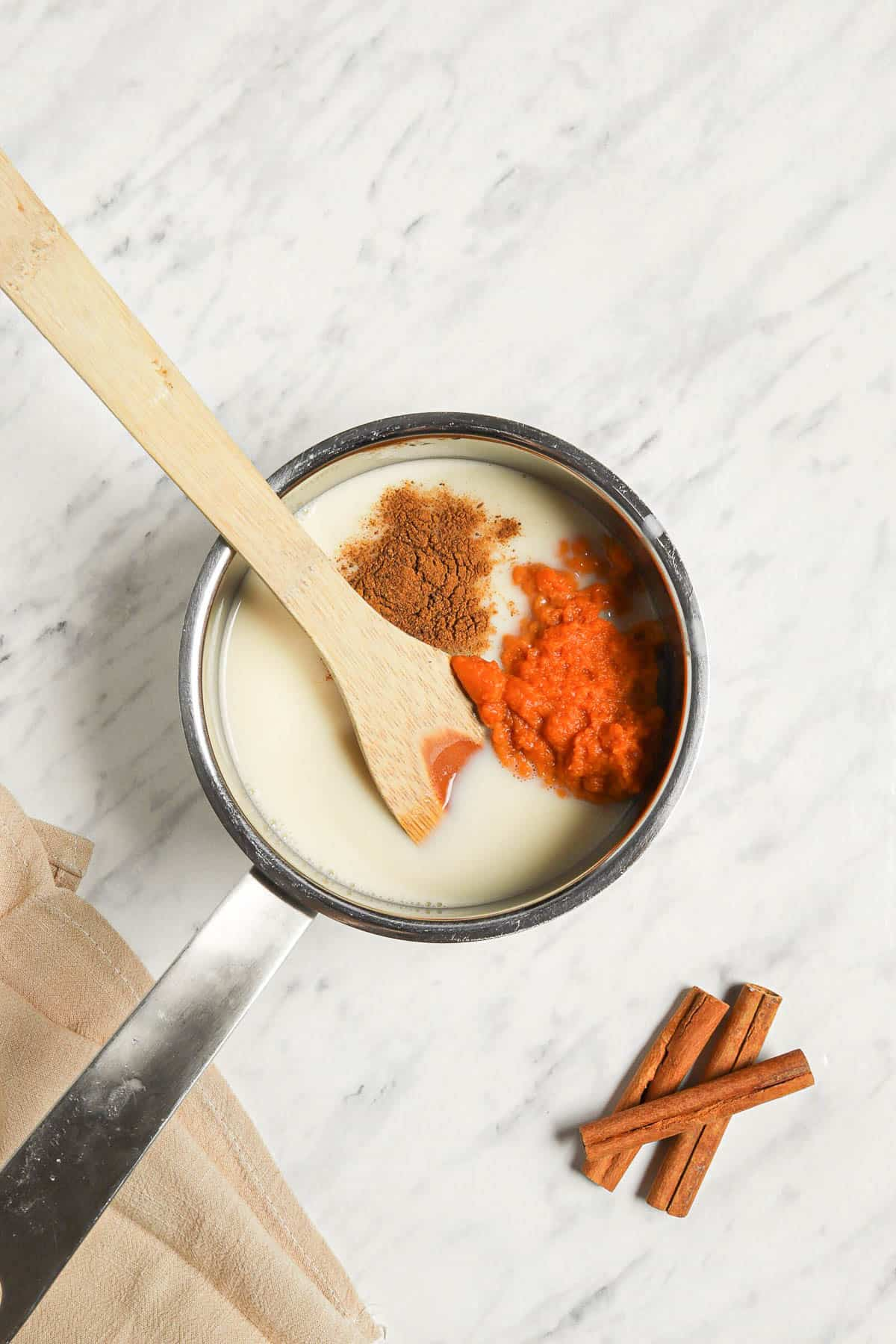 a saucepan with whole milk, pumpkin puree, pumpkin pie spice, maple syrup, and a wooden spoon