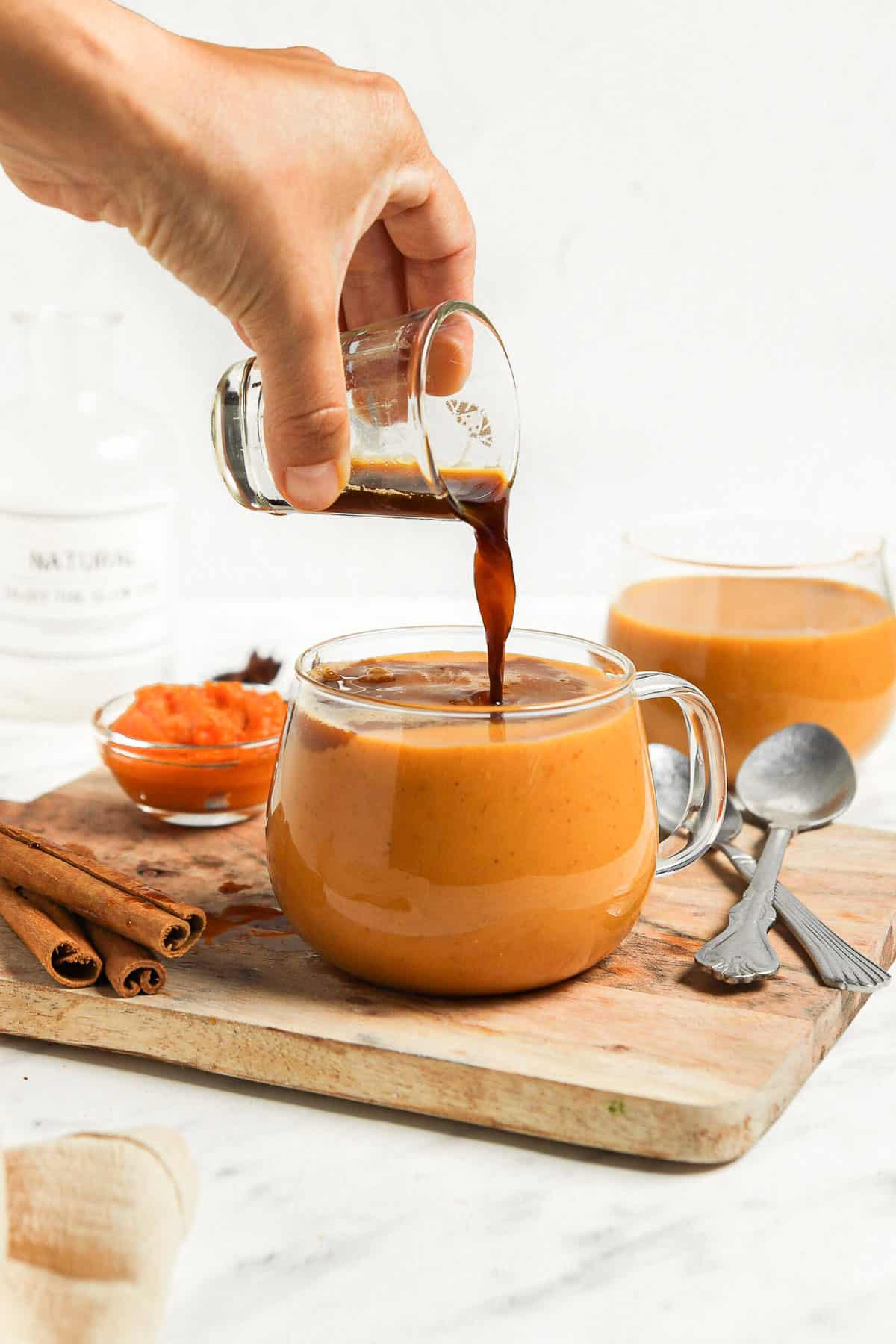 a clear glass coffee mug, filled with a homemade pumpkin spice latte, with a shot of espresso being poured into it