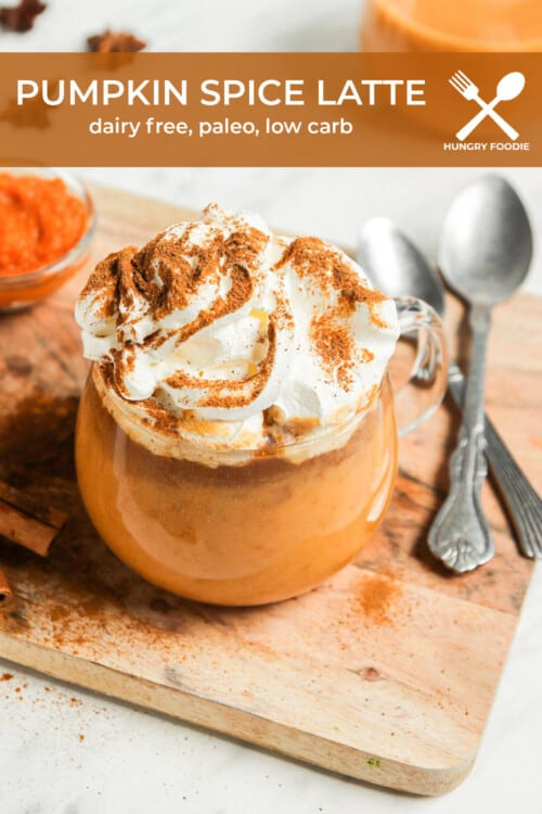 a clear glass mug with a pumpkin spice latte, topped with whipped cream and a sprinkle of pumpkin pie spice