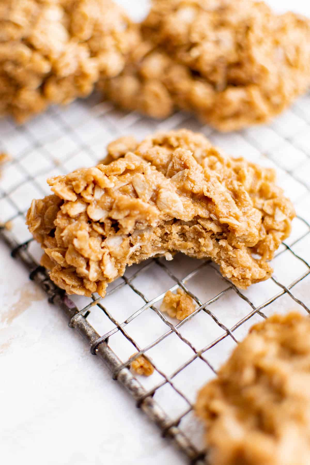 a cooling rack with peanut butter no bake cookies on it. One has a bite taken out of it