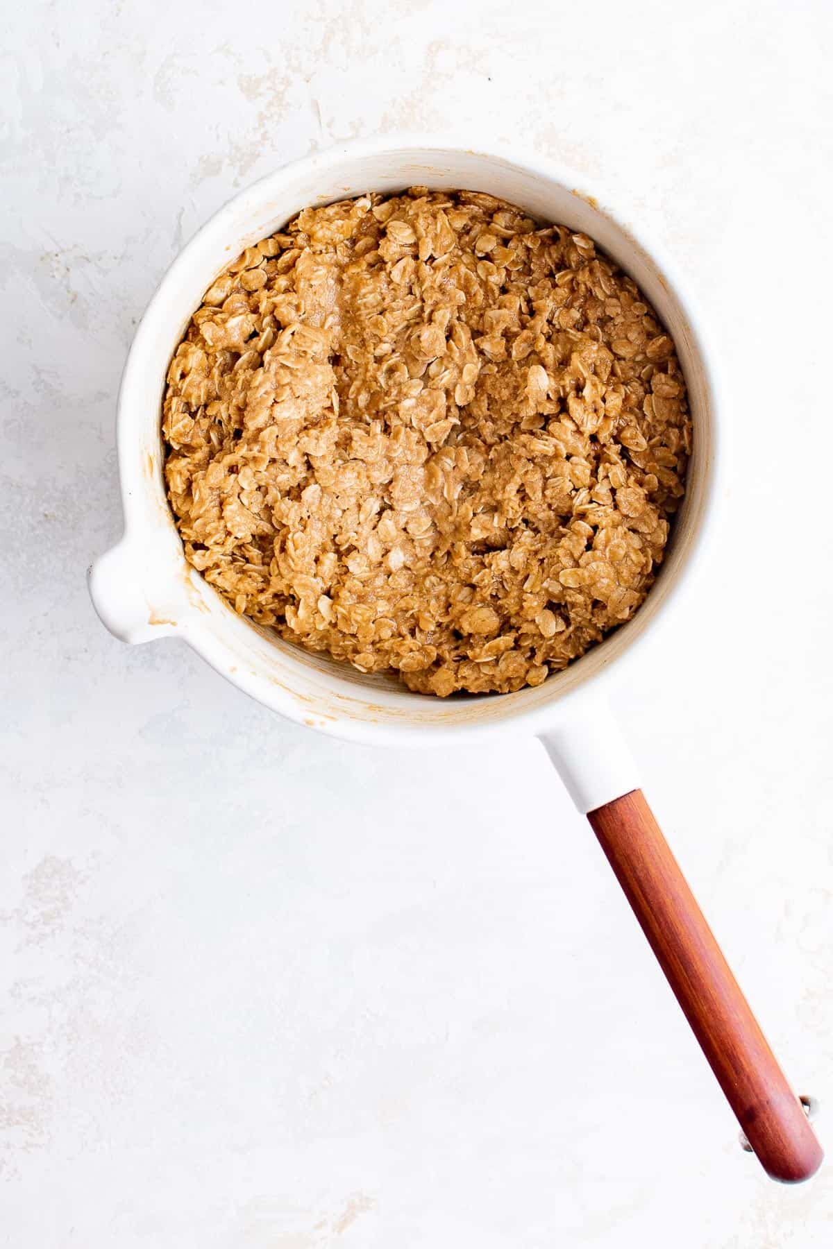 a sauce pan with melted butter, white sugar, brown sugar, peanut butter and oats in it
