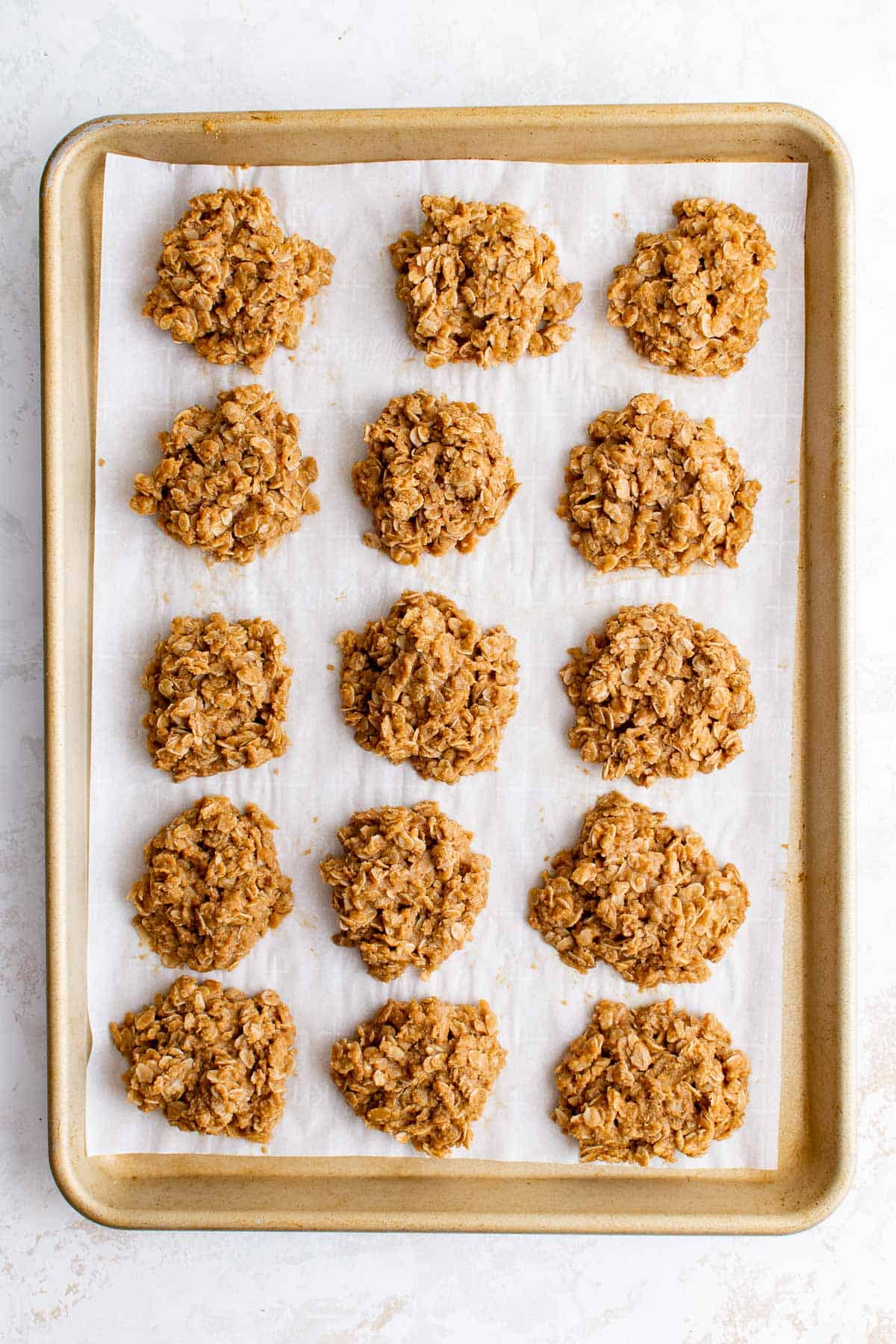 a baking sheet lined with parchment paper full of peanut butter no bake cookies